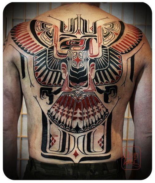 Tatuagem cobrindo as costas inteiras de um homem com o desenho tribal de uma águia vista de frente com as duas asas abertas lembrando muito inscrições indígenas antigas