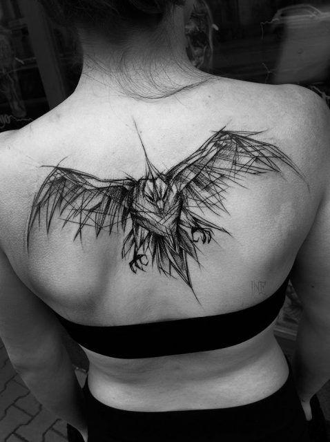 Tatuagem no centro das costas de uma mulher com o desenho de uma águia voando vista de frente feito como se fosse um esboço