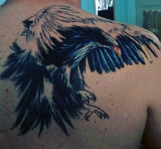 Tatuagem nas costas de uma águia com as asas abertas pronta para atacar