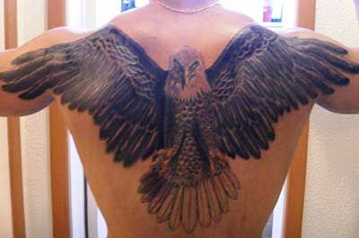 Tatuagem nas costas de uma águia com as asas abertas indo até o ombro do homem