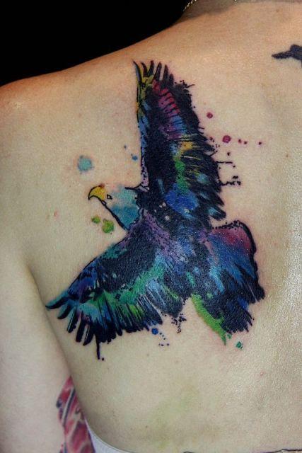 Tatuagem feita com aquarela de uma águia voando