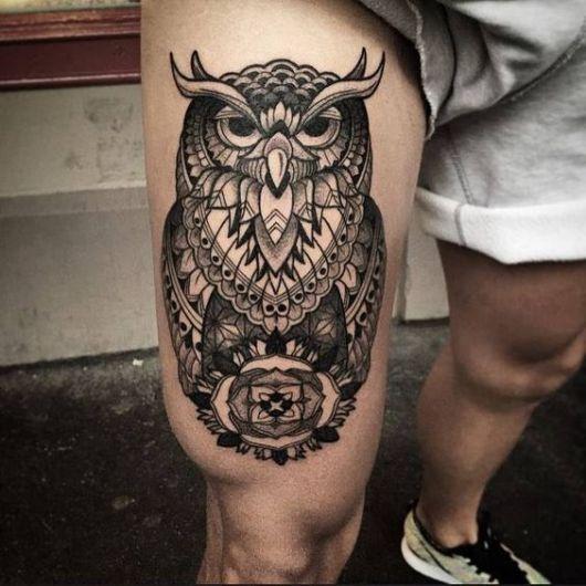 Tatuagem na coxa de um homem com uma coruja grande de aparência muito sábia e diversos elementos geométricos em sua composição