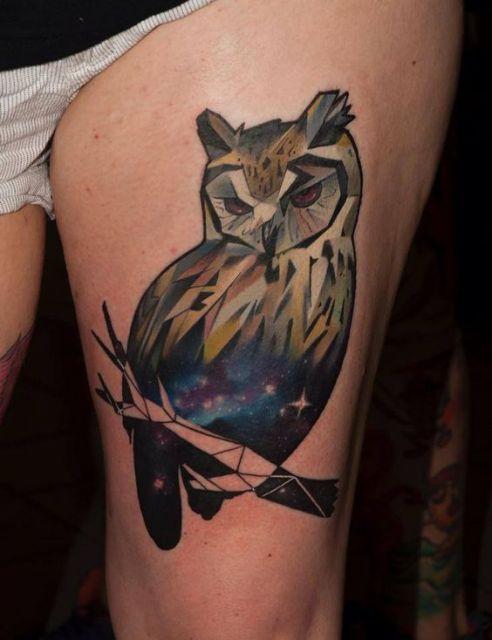 Tatuagem de uma coruja repousando em um galho. Seu interior é muito colorido, semelhante a um céu estrelado.