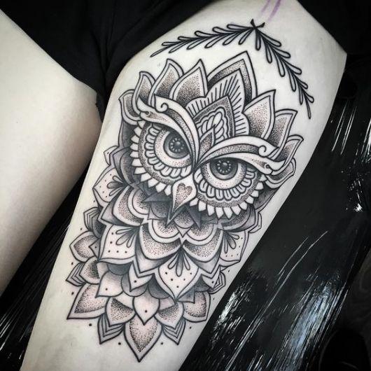 Tatuagem de coruja na perna feita em preto e branco com o rosto dela aparente e diversas mandalas ao redor