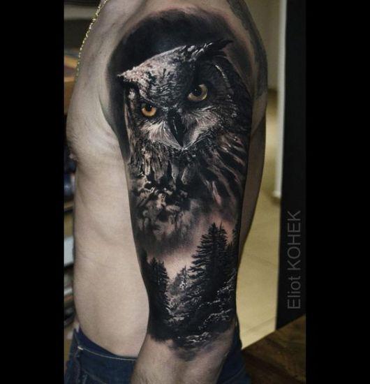 Tatuagem no braço com o desenho do rosto de uma coruja e abaixo dela uma floresta escura
