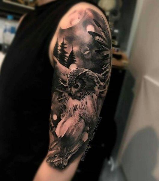 Tatuagem no braço com o desenho de uma coruja com asas abertas e atrás dela há o céu e uma floresta.