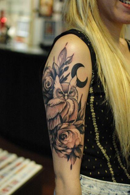 Tatuagem no braço de uma mulher com o desenho de uma coruja cercada de flores e a lua atrás dela