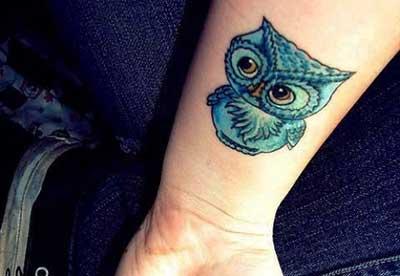 Tatuagem simples no pulso com uma coruja pintada de azul e olhos muito grandes