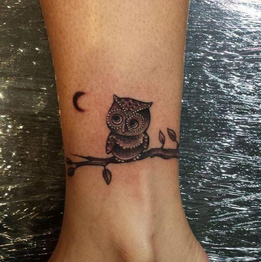 Tatuagem pequena feita no pulso com uma coruja repousando em um galho observando a lua.