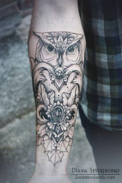 Tatuagem de uma coruja vista de frente com diversos adornos em seu corpo e também ao redor dela.