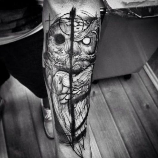 Tatuagem de uma coruja dividida no meio. Cada lado representa um aspecto diferente de sua personalidade.