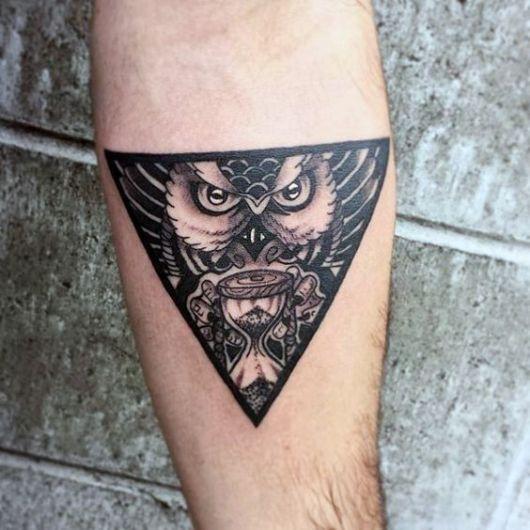 Tatuagem no antebraço de um triângulo invertido com uma coruja segurando um marca-tempo em seu interior.