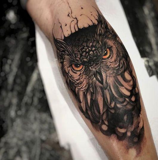 Tatuagem no antebraço de um homem com o desenho do rosto de uma coruja feita em preto e branco com os olhos alaranjados.