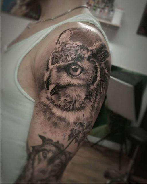Tatuagem feita no ombro de um homem com o rosto de uma coruja olhando para o lado de bico aberto