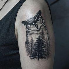 Tatuagem feita no ombro com o desenho do corpo de uma coruja cujo interior é preenchido por uma floresta
