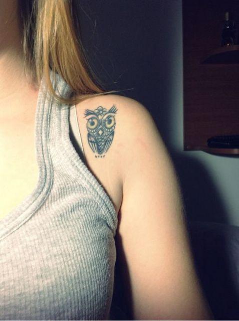 Tatuagem delicada de uma coruja feita na parte interna do ombro de uma moça.