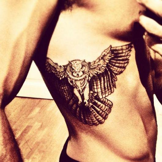 Tatuagem na costela de um homem com uma coruja de asas abertas.