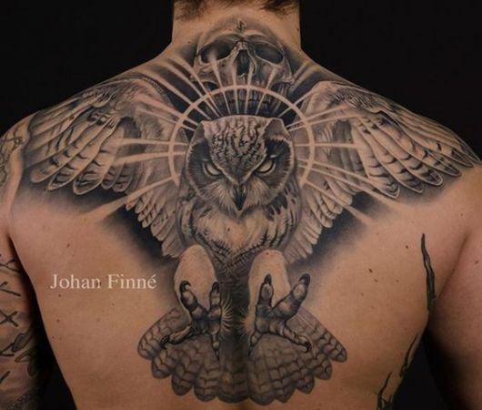 Tatuagem grande nas costas de um homem com uma coruja de asas abertas pronta para atacar com suas garras,