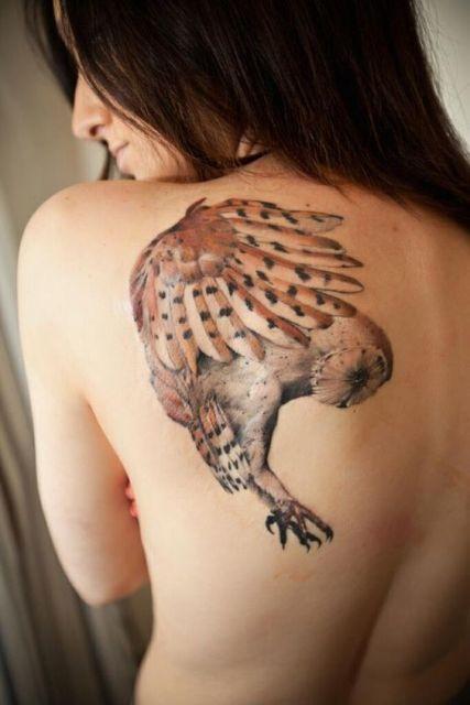 Tatuagem nas costas de uma mulher com uma coruja vista de lado enquanto voa.