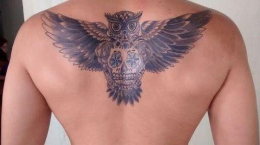 Tatuagem nas costas de um homem de uma coruja vista de frente com as asas abertas e uma caveira mexicana atrelada ao seu corpo