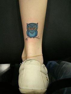 Tatuagem feita na parte de trás da perna com o desenho muito pequeno de uma coruja repousando em um galho