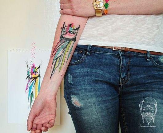 Tatuagem no antebraço com o desenho de uma coruja cujo corpo é feito de três penas grandes muito coloridas
