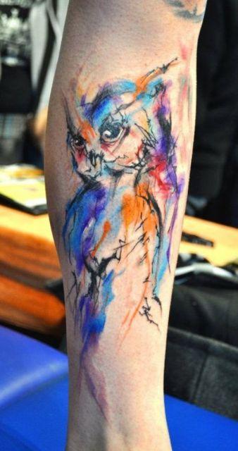 Tatuagem grande de coruja feita com aquarela em diversas tonalidades diferentes