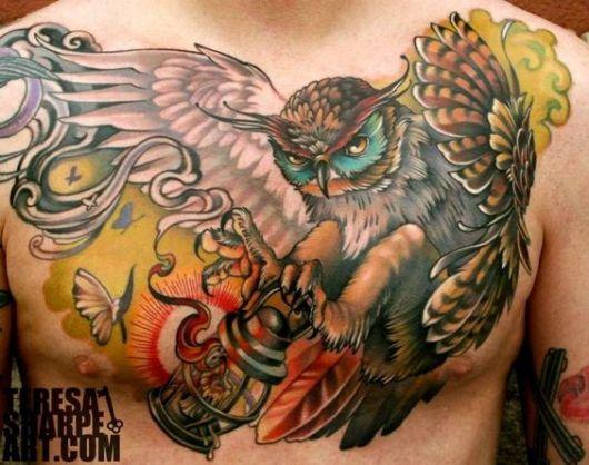 Tatuagem grande no peito de um homem com o desenho de uma coruja de asas abertas segurando um lampião em suas patas