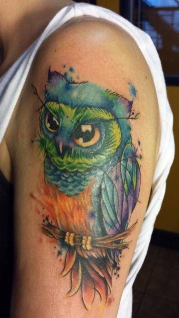 Tatuagem de uma coruja repousando em um galho pintada com aquarela nos tons de azul, verde, roxo e laranja.