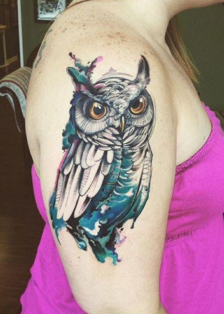 Tatuagem no braço de uma mulher de uma coruja pintada parcialmente de azul.
