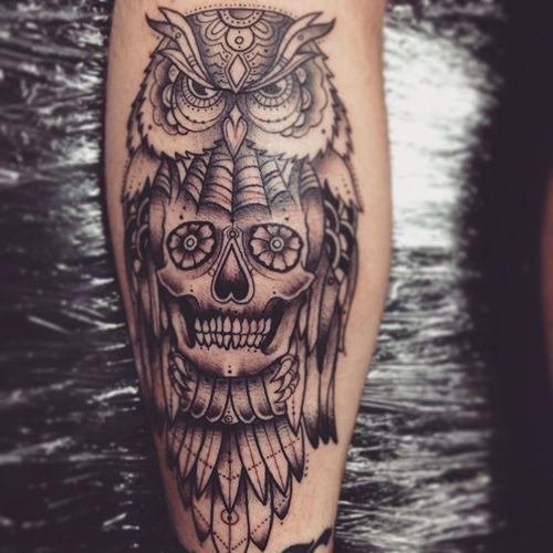Tatuagem rica em detalhes de uma coruja com aparência de brava cujo corpo possui uma caveira onde seria sua caixa torácica.