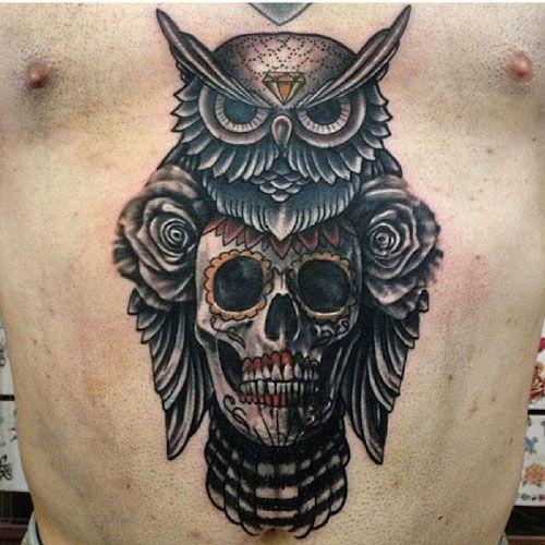 Tatuagem de uma coruja com uma caveira acoplada no centro de seu corpo.