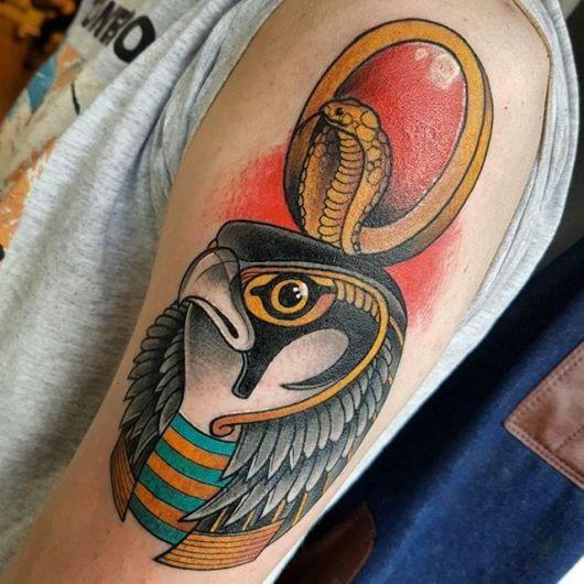 Tatuagem do rosto do Deus Rá, que parece um falcão com um adorno vermelho acima de sua cabeça.