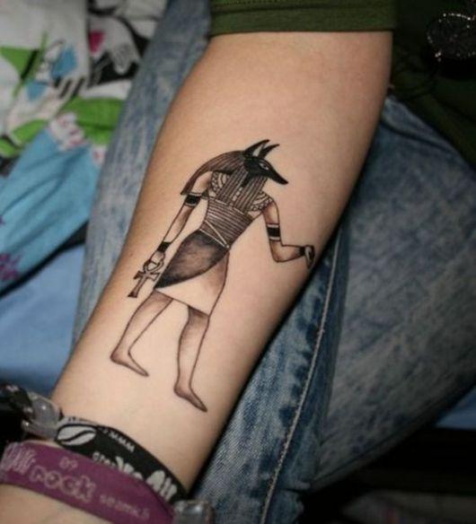 Tatuagem do deus Anúbis de pé olhando para o lado enquanto segura uma cruz Ankh
