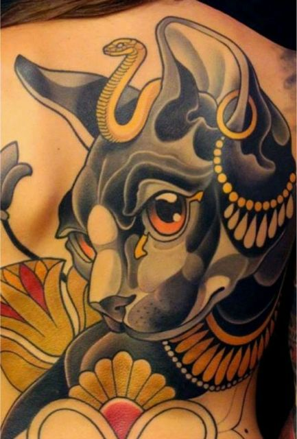 Tatuagem grande de um gato preto com diversos adornos feita nas costas de uma mulher