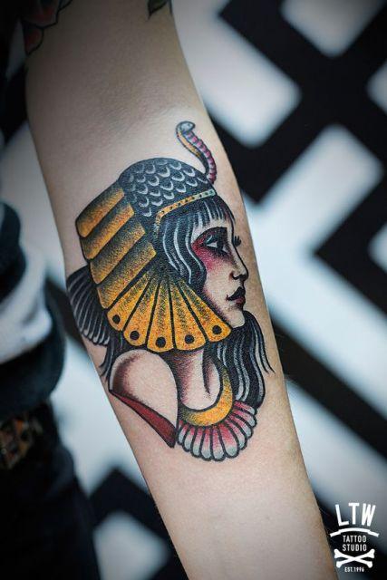 Tatuagem colorida de uma deusa egípcia feita no antebraço de uma mulher.