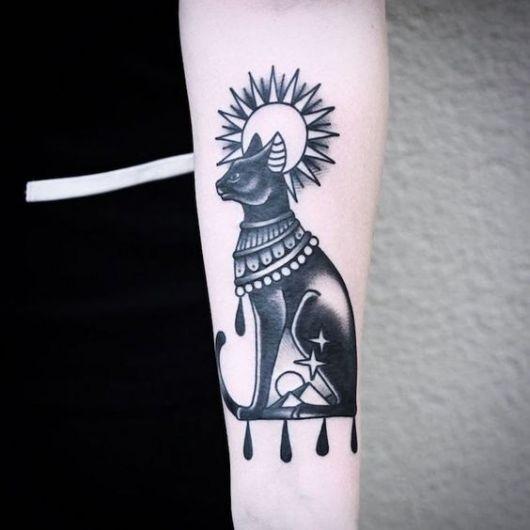 Tatuagem de um gato preto sentado em posição de guarda com o sol ao fundo.