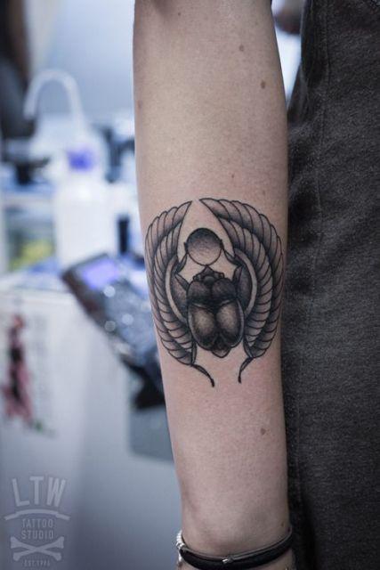 Tatuagem em tons de cinza de um escaravelho carregando o sol em suas patas.