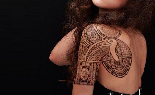 Tatuagem nas costas e parte do braço de uma mulher com diversas formas que constituem adornos egípcios.