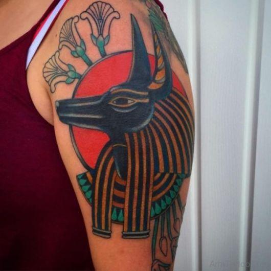 Tatuagem colorida do rosto de Anúbis com o sol ao fundo.