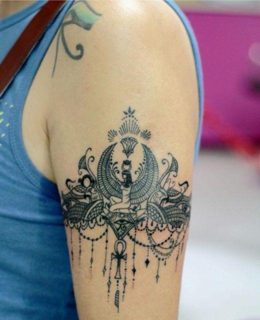 Tatuagem delicada no braço de uma mulher com diversos símbolos símbolos do Egito Antigo, como o olho de hórus e a deusa ísis.
