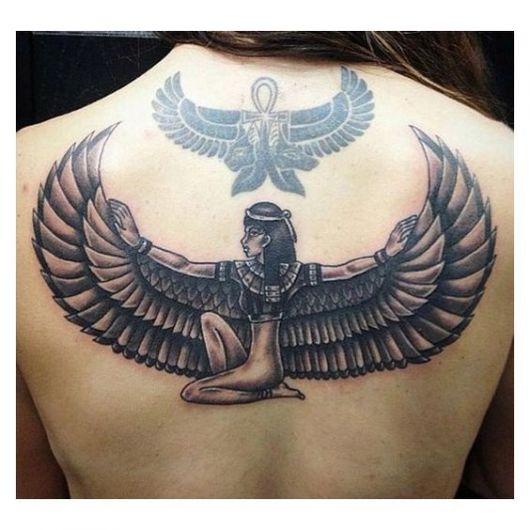 Tatuagem grande nas costas de uma mulher da deusa Isís sentada no chão com os braço estendidos.