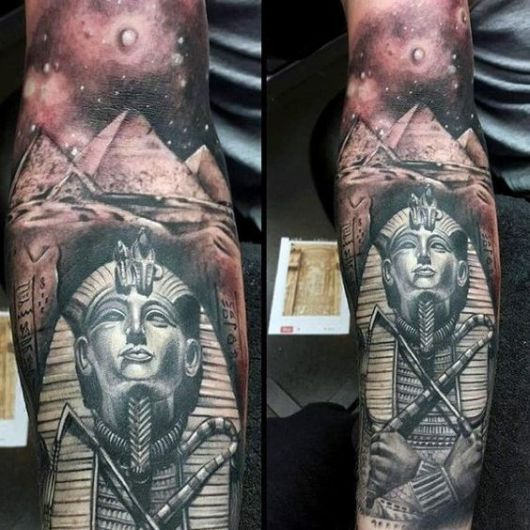 Tatuagem de uma esfinge com as pirâmides e o céu detalhados ao fundo
