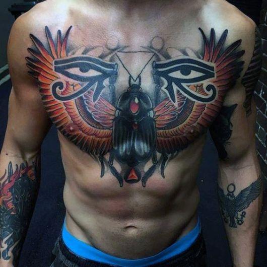 Tatuagem no peito de um homem com um escaravelho grande e dois olhos de hórus, um de cada lado.