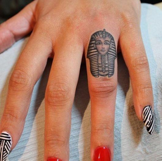 Tatuagem pequena do rosto de uma esfinge feita no dedo anelar.