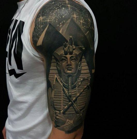 Tatuagem realista cobrindo a parte superior do braço de um homem com o desenho de uma esfinge e as pirâmides com um céu estrelado ao fundo.