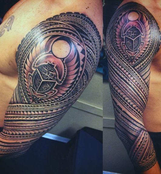 Tatuagem cobrindo o braço inteiro de um homem feita a partir de diversas formas e símbolos que compõem uma unidade.