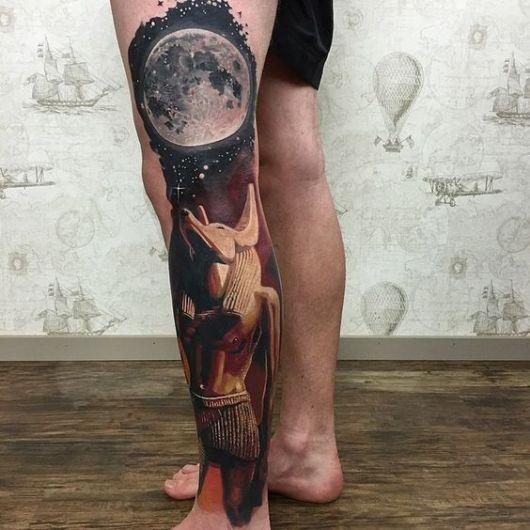 Tatuagem na perna de um homem com o desenho do deus Anúbis olhando para a lua.