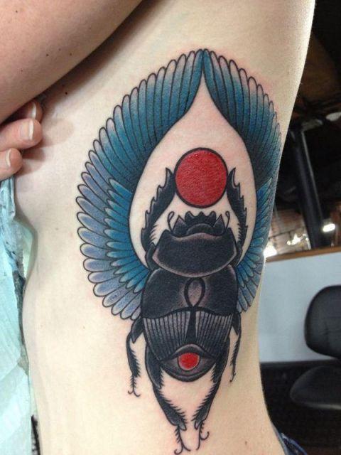 Tatuagem na costela com o desenho de um escaravelho com asas e o sol entre suas patas.