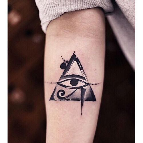 Tatuagem feita no antebraço com o desenho do olho de hórus dentro de um triângulo